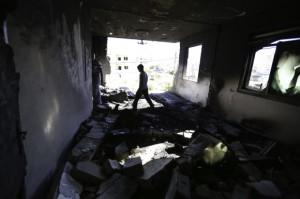 Un vecino camina a través de la sala de estar del segundo piso que fue completamente destruida por la explosión durante la noche. (Foto: Kelly Lynn)
